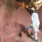 Shrine Interior: Adebisi Akanji puts the final layer of red oxide on the sculpted chairs in the ceremonial room. The red oxide gives both colour and a protective finish.