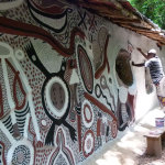 Under the guidance of artist Sangodare Ajala, Kejenyo Kenny paints Sacred Shrine art on the exterior wall.